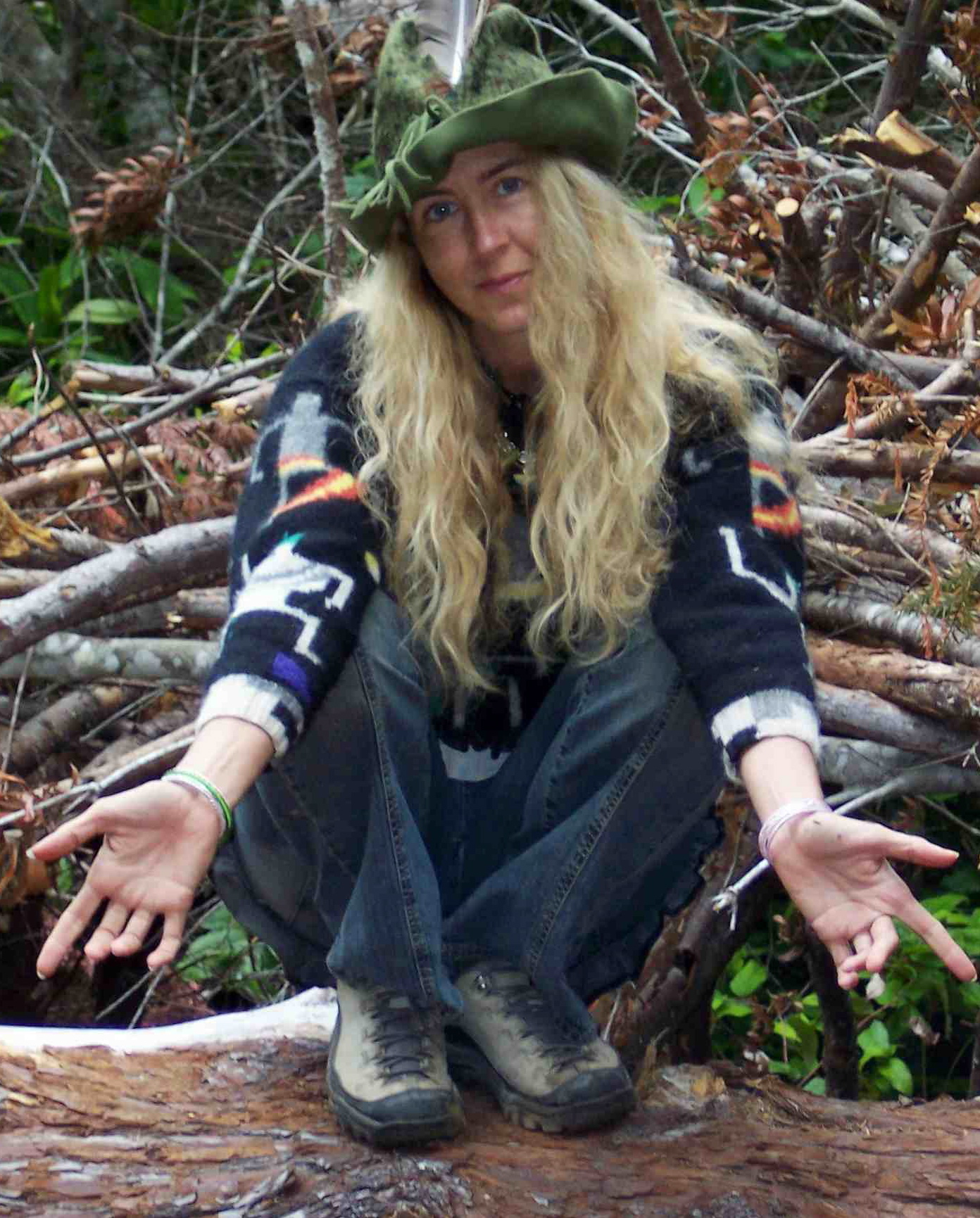 A faery woman dons her elfin hat and squats on a tree trunk, hands open.