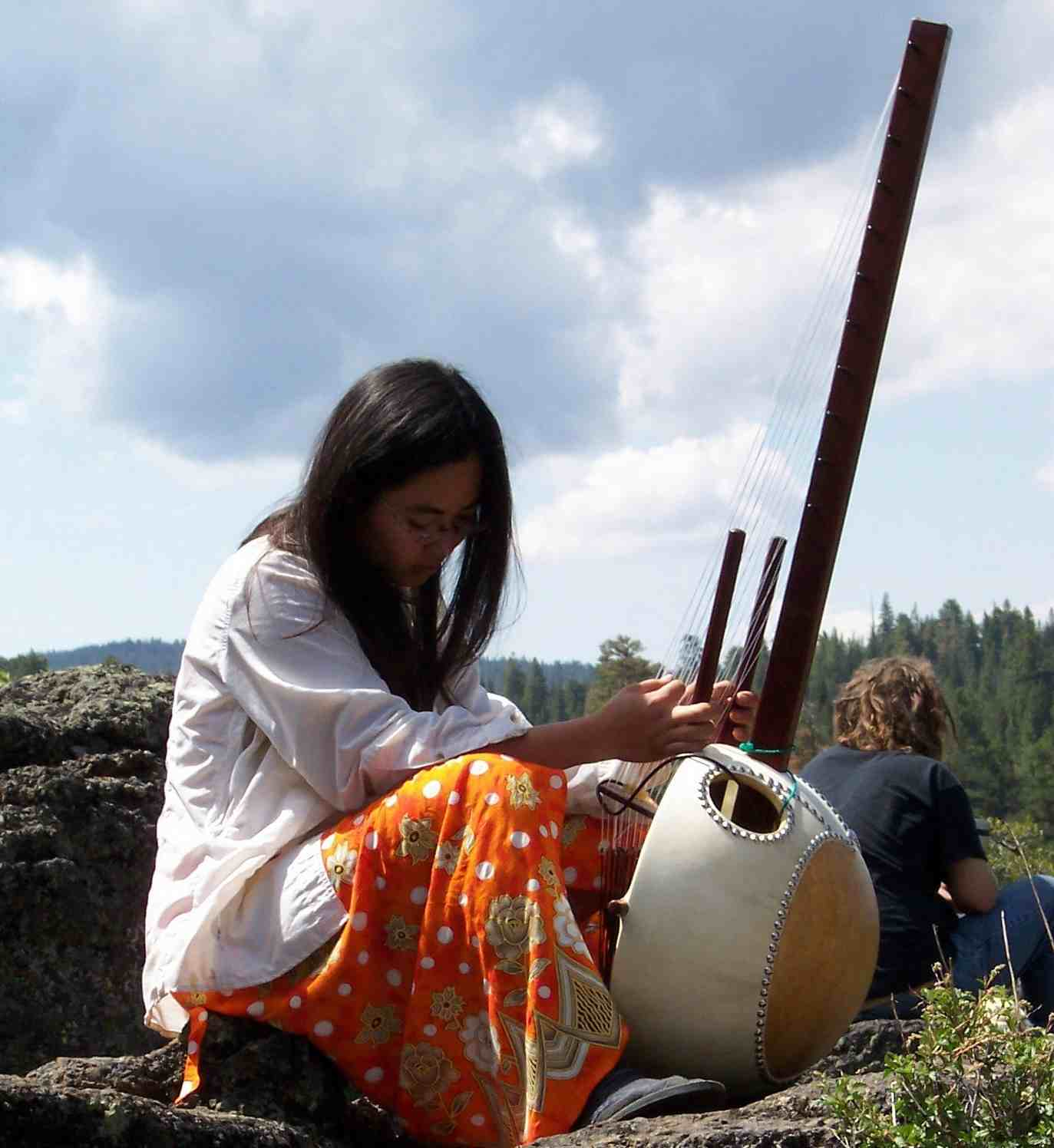 A faery woman musician prepares to play her instrument.